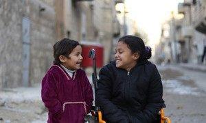 Una niña siria que perdió el movimiento de sus piernas tras un bombardeo, comparte con su hermana pequeña en Aleppo.