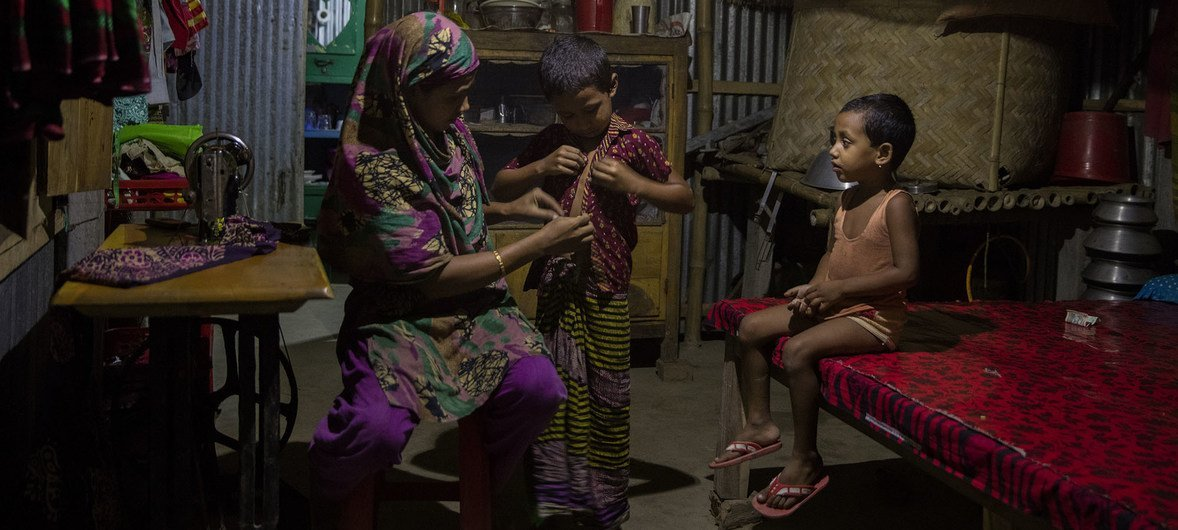 A mother helps her children get ready for bed in Bangladesh. October 2016.