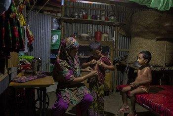 Una mujer ayuda a sus hijos a alistarse para dormir en Bangladesh.