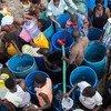 La gente afectada por el huracán Matthew, en Haití, traslada agua limpia en cubos para poder llevarla a casa.