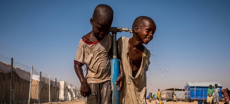 Des enfants jouent avec de l'eau lors d'une récréation dans une école soutenue par l'UNICEF dans le camp de déplacés de Bukasi, à Maiduguri, dans l'Etat Borno, au Nigéria.