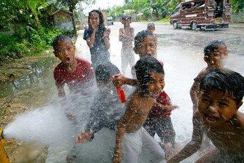 Un grupo de niños juegan con el agua de una boca de incendio en la ciudad de Cobato, en Filipinas.