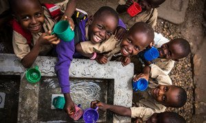 Children fill their cups at a water point built by UNICEF at Kanyosha III primary school in Bujumbura, Burundi.