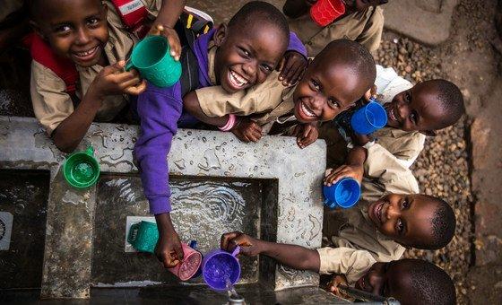 Des enfants remplissent leur gobelet à un point d'eau construit par l'UNICEF dans une école primaire à Bujumbura, au Burundi.