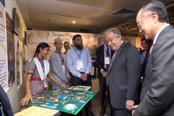 Secretário-geral António Guterres e o presidente do Grupo Banco Mundial, Jim Yong Kim, falam com crianças em uma exposição em Daca.