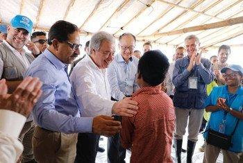 Katibu Mkuu wa UN António Guterres (mwenye shati jeupe na mkono begani mwa mtoto) Rais wa Benki ya Dunia Jim Yong Kim, (kushoto kwake) na Kamishna Mkuu wa UNHCR Filippo Grandi (kushoto kwa Jim) wakikutana na mvulana kwenye kambi ya wakimbizi ya Cox's Bazar leo tarehe 2 Julai 2018