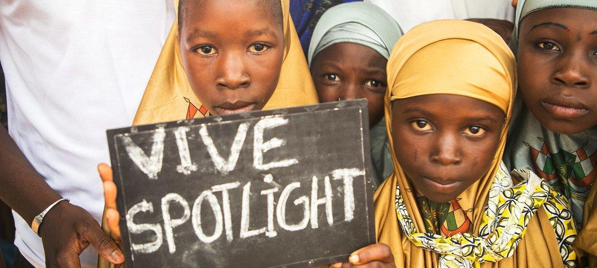 尼日尔丹加村的年轻女孩举着一个支持聚焦倡议的标志,聚焦倡议是欧盟和联合国支持可持续发展目标的基金。