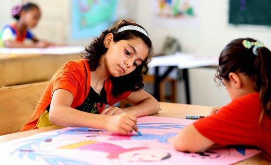 Una niñas colorean durante un campamento de verano en la escuela Deir Al Balah