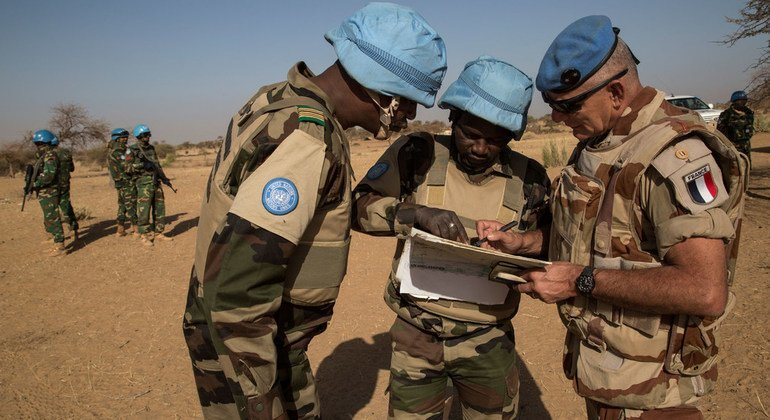 Brigadier General Christian Thiebault (right), MINUSMA Force Chief of Staff, looks at a map along with two officers from the Niger Battalion during a military operation in Ansongo, in eastern Mali, in February 2015.