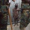 在南苏丹里尔的联合国南苏丹特派团基地附近的临时营地,一名儿童站在来自加纳的维和人员后面。约有2000名平民因最近的冲突在营地中避难。