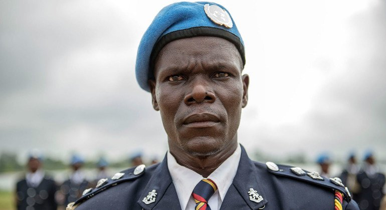 A Kenyan police officer serving with the UN Mission in Liberia (UNMIL) stands at attention for the national anthem during an awards ceremony at Camp Clara, in Monrovia, in May 2014. .