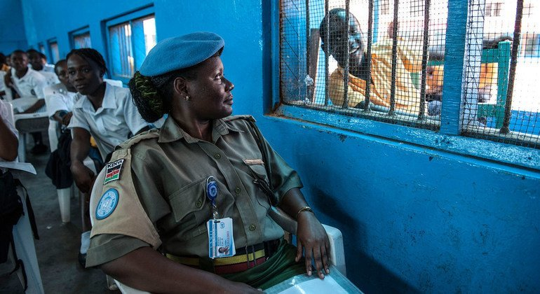 Ruth Kefa, a Kenyan corrections officer with the UN Mission in Liberia (UNMIL), shares a laugh with a student at JJ Roberts High School during an outreach event in the capital, Monrovia, in October 2012.