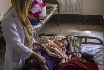A midwife checks an exhausted new mother, who is recuperating next her 3-day-old sleeping infant daughter at the UNICEF-supported birthing centre in the Kutupalong camp for Rohingya refugees, in Cox's Bazar, Bangladesh, October 2017.