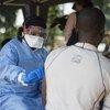 Juni 20, mhudumu kutoka WHO anatoa chanjo kwa mwanaume nchini Jamhuri ya Kidemokrasia ya Kongo, DRC kijiji cha Bosolo