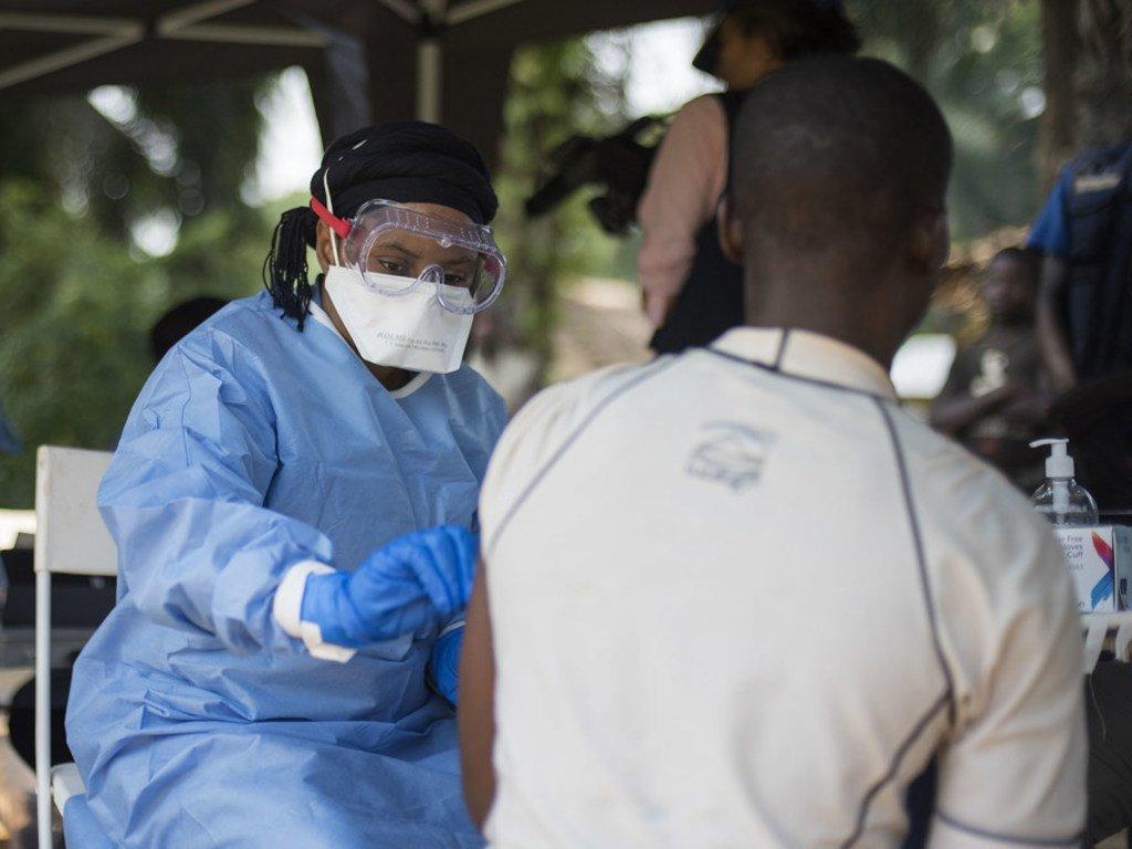 Le 20 juin 2018, un membre de l'OMS vaccine un homme contre le virus Ebola dans le village de Bosolo, en RDC.