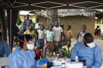 Un grupo de personas mira como vacunan contra el Ébola en el pueblo de Bosolo, República Democrática del Congo.