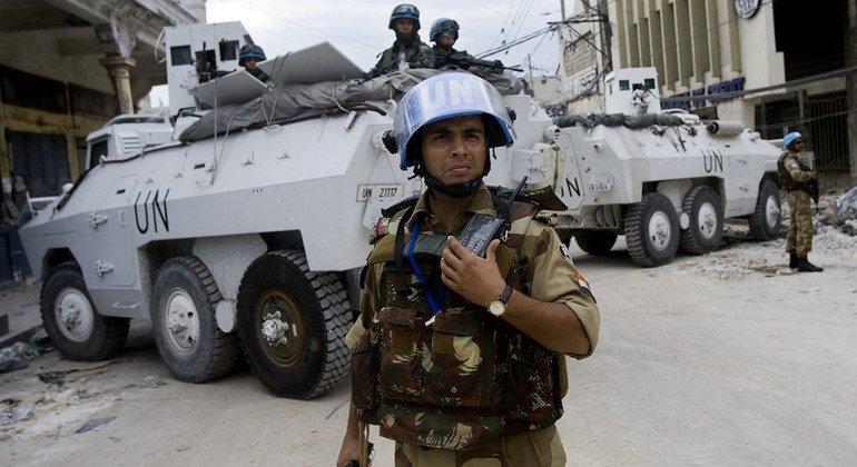 Un oficial de la Unidad de Policía Constituida de la India (FPU), que trabaja con el personal brasileño de mantenimiento de la paz de las Naciones Unidas, ayuda a asegurar el perímetro de un banco en el centro de Puerto Príncipe, Haití.