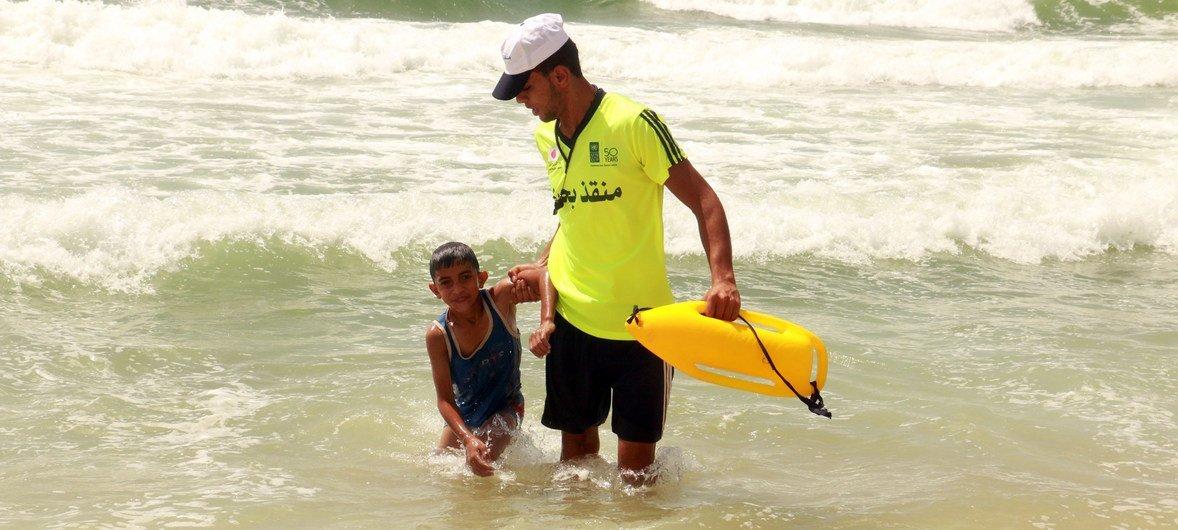 Un joven ayuda a un niño a salir del agua en una playa de Gaza