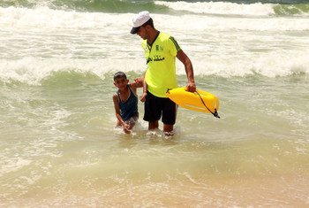 A young man working as a lifeguard helps a child out of the water on a Gaza beach.