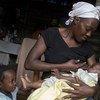 Masita Lemorin, âgée de 26 ans, nourrit son fils de 4 mois, Nathanael, tandis que sa fille Anne regarde sa maison à Quicroit, un village situé au sud de Port-au-Prince, en Haïti.