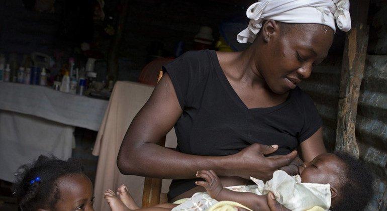 Masita Lemorin, de 26 años, da el pecho a su bebé de 4 meses, Nathanael, mientras su hija Anne les observa en su casa de Quicroit, un pueblo aislado en las montañas al sur de Puerto Príncipe en Haití