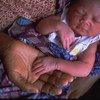 Un recién nacido duerme en los brazos de su madre en un centro de salud de Accra en Ghana.
