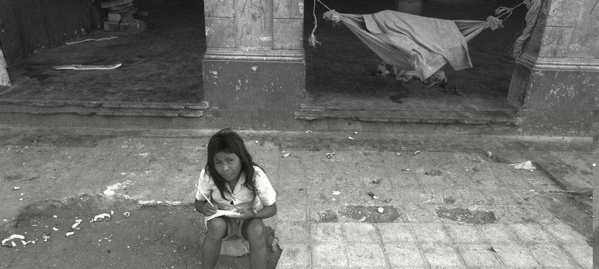 In downtown Managua, the capital of Nicaragua, a young displaced girl writes in a notebook in front of a formerly abandoned building where she lives with her family.