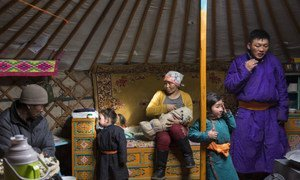 Thirty-two year old Delgermurun breastfeeds her eight-day-old baby amidst her family in a ger, Alag-Erdene, Mongolia.
