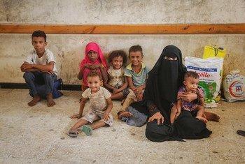 سيدة وأطفالها ينتظرون توزيع مساعدات طارئة مدعومة من اليونيسف في الحديدة، اليمن. يونيه حزيران 2018.