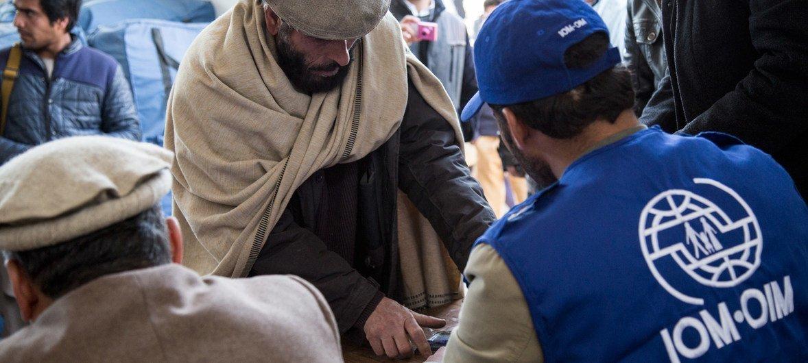 国际移民组织工作人员正在为前来领取援助的阿富汗受灾家庭进行登记。