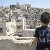 Eight-year old Hamid looks out over the old city of Hebron from the roof of his house in Palestine.