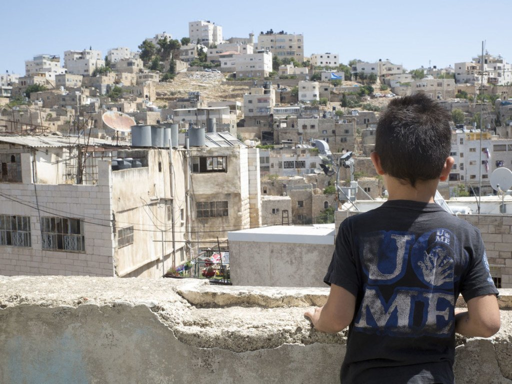 12 juillet 2018 : Hamid, 8 ans, regarde, depuis le toit de sa maison, la vieille ville d'Hébron. La circulation des personnes et l'accès à l'école des enfants sont affectés par les points de contrôle situés dans la vieille ville de Cisjordanie.