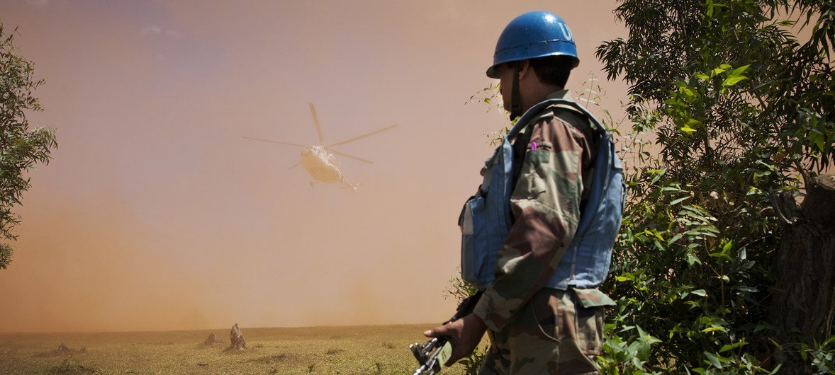 An Indian Peacekeeper stands near helipad as a MONUSCO helicopter carrying DRC Minister of Communication Lambert Mende lands near Kanyabayonga COB, the 5th of June 2014.