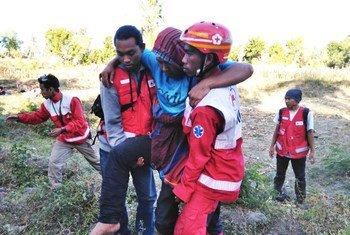 一名在8月5日地震中受伤的伤员在红十字会工作人员的帮助下从龙目岛撤离。