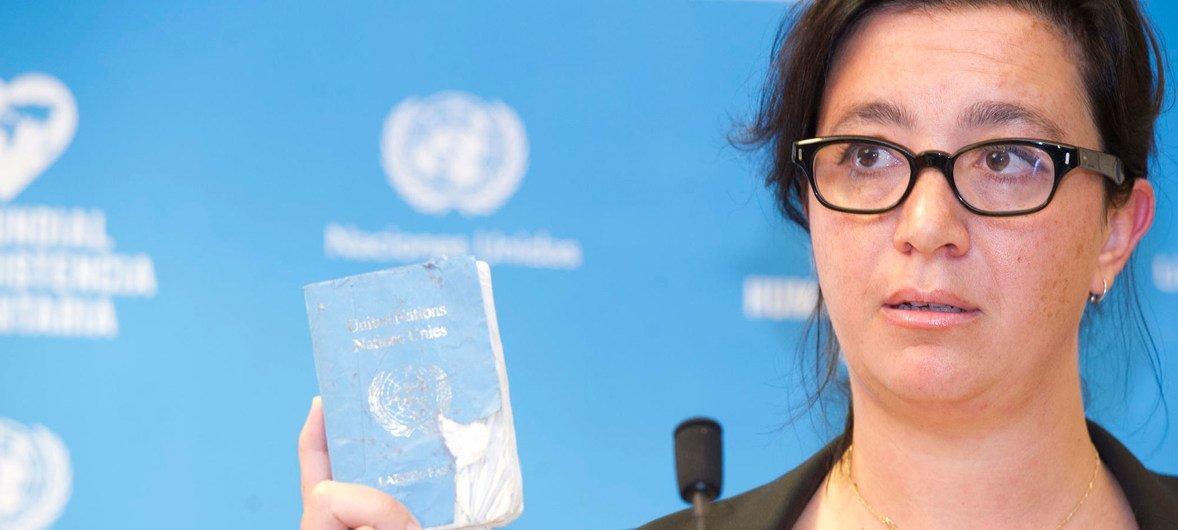 Elpida Rouka, ancienne cheffe de l'Envoyée spéciale pour la Syrie et survivante de l'attentat contre l'hôtel Canal à Bagdad le 19 août 2003, montre son Laissez Passer de l'ONU lors de la Journée mondiale de l'aide humanitaire à Genève.