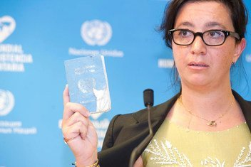 Elpida Rouka, Senior Political Officer, Office of the Special Envoy for Syria and survivor of the bombing of the Canal Hotel in Baghdad on 19 August 2003 shows her UN Laisser Passer during the Solemn Commemoration Ceremony of the World Humanitarian Day, Palais des Nations, Geneva.