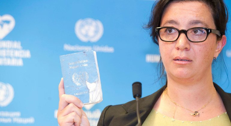 Elpida Rouka, Senior Political Officer, Office of the Special Envoy for Syria and survivor of the bombing of the Canal Hotel in Baghdad on 19 August 2003 shows her UN Laisser Passer during the Solemn Commemoration Ceremony of the World Humanitarian Day, Palais des Nations, Geneva (August 2016).