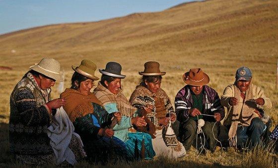 نساء ورجال من السكان الأصليين في بيرو يغزلون ملابس من صوف الألبكة.