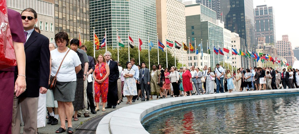 United Nations staff members march around the Secretariat in New York to express their distress over the bombing of the UN Headquarters in Baghdad on 19 August. In the background are the flags of the United Nations members. (26 August 2003)