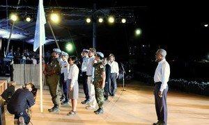 Katibu Mkuu wa UN Kofi Annan akiwa amesimama wakati bendera ya UN ikishushwa tayari kupandisha ya Timor Mashariki huko mjini Dili