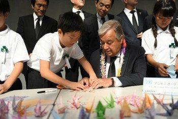 El Secretario General António Guterres dobla grullas de origami con jóvenes líderes japoneses en el Monumento a la Paz de Nagasaki.