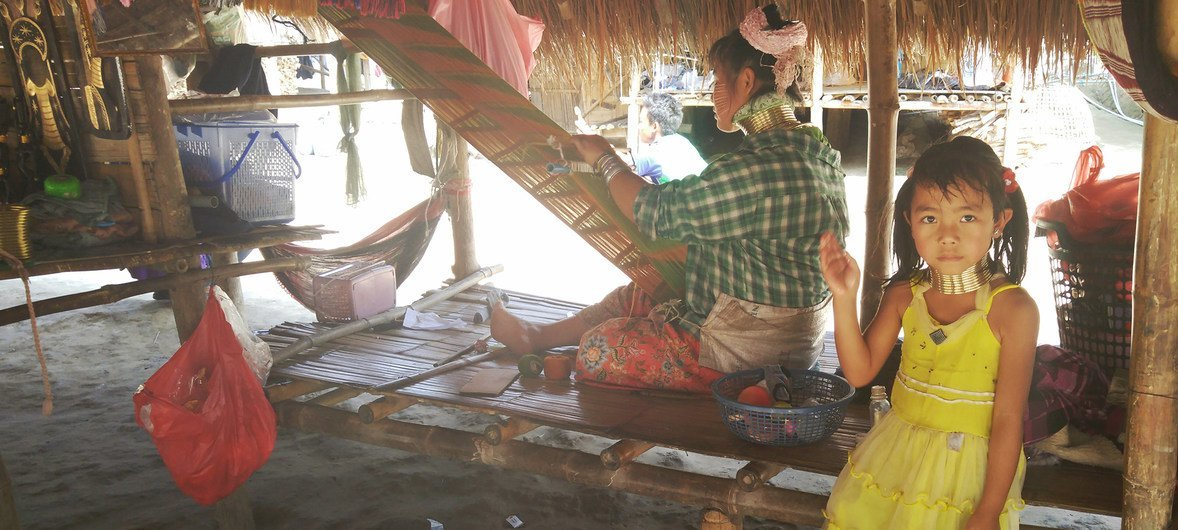 A Karen woman weaves as her daughters play near her in Chiang Rai, Thailand.