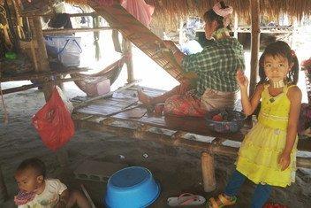 泰国清莱,一名克伦族(Karen)土著人妇女正在织布,她的女儿在一旁玩耍。