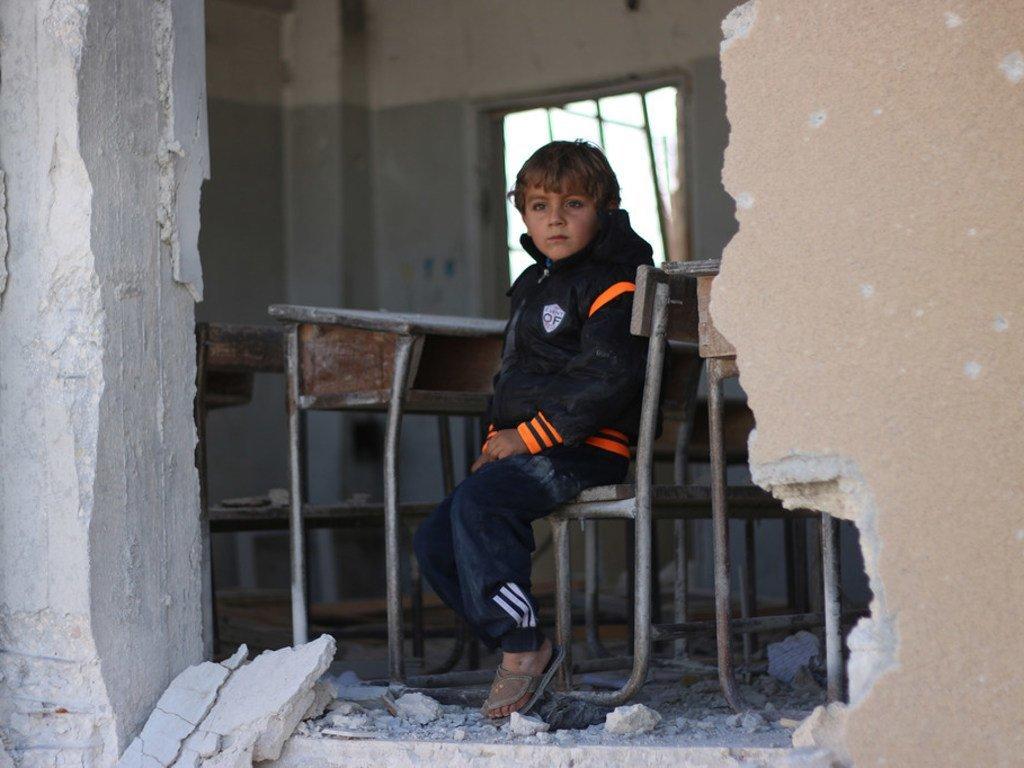 2016年,叙利亚伊德利卜,一名男孩坐在被战火摧毁的教室课桌前。