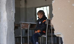 A child sitting at a desk in a school that was attacked, in Idlib, Syria. 2016.