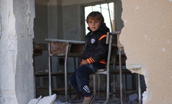 在叙利亚伊德利卜,一名男孩坐在因炮火而受损的教室的书桌上。