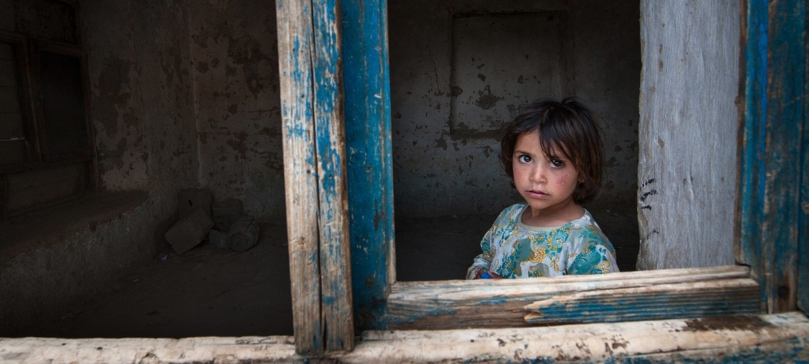 A young girl looks through a paneless window frame near Kabul, in Afghanistan, 2013. Civlilians in Afghanistan have borne the brunt of an almost 20 years of conflict.