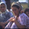 A boy rests against a woman in a camp of people displaced from Srebrenica, at the Tuzla airport in Bosnia and Herzegovina, 1995.