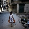 Msichana akiwa amebeba magudulia ya maji akipita karibu na rundo la taka, katika barabara moja mjini Aleppo, Syria.