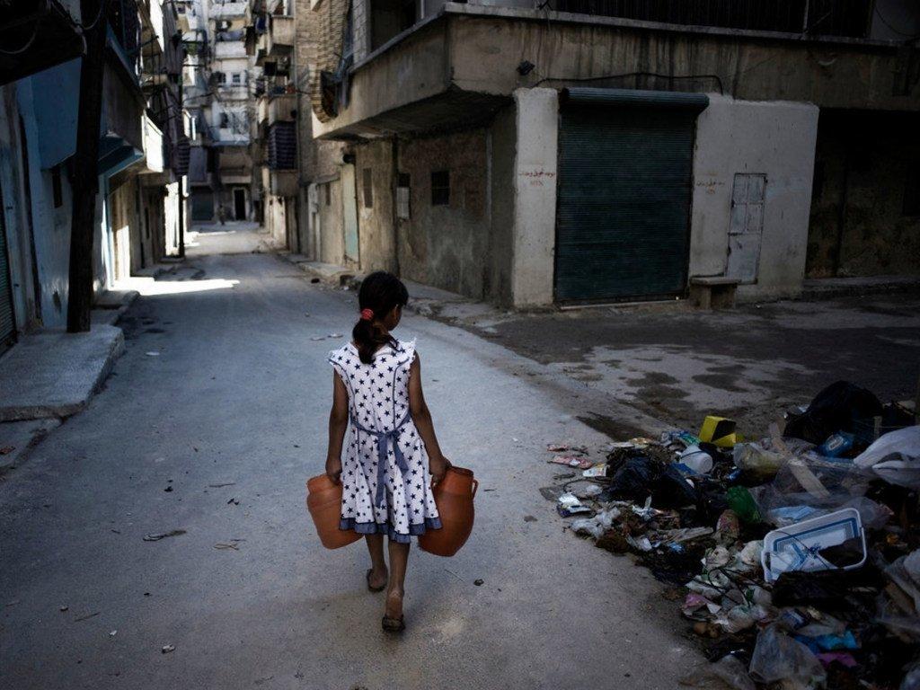 Une jeune fille syrienne transportant des jerrycans d'eau passe devant une pile de débris dans une rue d'Alep, en Syrie (archive).